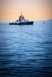 Boat at sea on sunset. Fishing freighter in the calm evening. Royalty Free Stock Photos