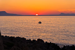 Boat on sea at sunset, island of Crete Stock Image