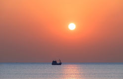 Boat on the sea at sunset Stock Photos