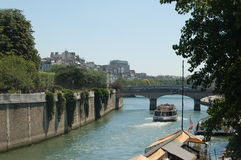 A boat on the Seine River in Paris. A boat riding along the Seine River in Paris, France Royalty Free Stock Images