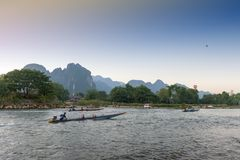 Boat service for tourists in Nam Song River, Vang Vieng, Lao PDR. Vang Vieng, Laos - November 2015: Boat service for tourists in Nam Song River, Vang Vieng, Lao Royalty Free Stock Images