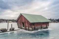 Boat shack. Beautiful red fishing shack and boat house surrounded by ice Royalty Free Stock Image