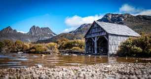 The Boat Shed on the picturesque Dove Lake at Cradle Mountain, Tasmania. Waking up to a beautiful sunrise and capturing the moment of the fog lifting gently stock photography