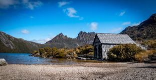 The Boat Shed on the picturesque Dove Lake at Cradle Mountain, Tasmania. Waking up to a beautiful sunrise and capturing the moment of the fog lifting gently stock photo