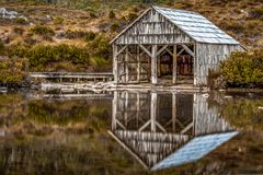 The Boat Shed on the picturesque Dove Lake at Cradle Mountain, Tasmania. Waking up to a beautiful sunrise and capturing the moment of the fog lifting gently royalty free stock photo