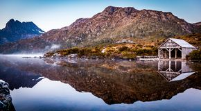 The Boat Shed on the picturesque Dove Lake at Cradle Mountain, Tasmania. Waking up to a beautiful sunrise and capturing the moment of the fog lifting gently royalty free stock image