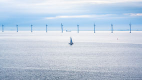 Boat and ship near offshore wind farm in morning Royalty Free Stock Photos