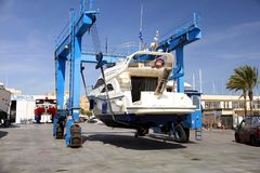 Yacht on shipyard travelift prepared for maintenance. Boat in a shipyard of Alicante city after cleaning the hull and ready for made reparations Stock Image