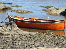 Boat at shore. A small boat is docked on a stone shore royalty free stock images