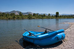Boat on the shore. Blue boat on the shore of Snake River, Wyoming on a clear summer day royalty free stock image