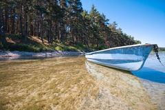 A boat by the shore of a large lake. Pine forest. Sunny weather. Clear clear water Royalty Free Stock Photography