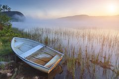 Boat on the shore of a misty lake on a summer morning stock images
