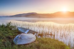 Boat on the shore of a misty lake on a summer morning Stock Photos