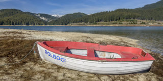 Boat on the Shore. Old boat tied on the shore of Boloboci Lake, in Bucegi Natural Park, Romania. Outdoor image shot in natural light Royalty Free Stock Photo