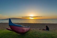 Boat on Shoreline. Sea canoe on shoreline while paddler takes a break to enjoy the sunset in Maui Royalty Free Stock Photos