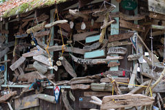 Boat signs and name plates with shells decorating a driftwood hut in Canada`s Inside Passage Royalty Free Stock Images