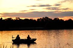 Boat silhouette. Silhouette of two people in a motorboat at sunset. The boat is idling along in the last light of day. The golden colors of the sky are reflected royalty free stock image