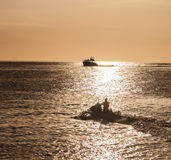 Boat silhouetted in the setting sun Royalty Free Stock Photos