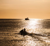 Boat silhouetted in the setting sun Royalty Free Stock Image