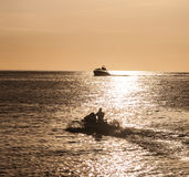 Boat silhouetted in the setting sun Stock Photos