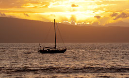 Boat Silhouetted in the Sunset Stock Images