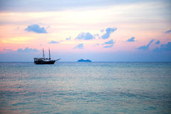 Boat silhouetted by the sunset. Boat in silhouette in front of a landscape of sunset colors over the ocean Stock Photos