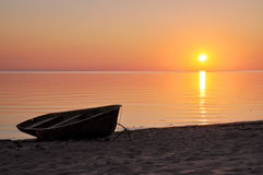 Boat silhoutte on the seashore at sunset. Stock Images