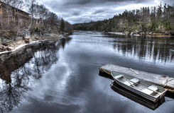 Boat Sits at Dock. Row boat sits at dock on a calm river Royalty Free Stock Photo