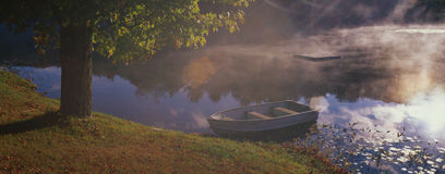 boat sitting at the edge of a pond Stock Photos