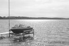 Boat sitting in lake. Boat in lake on hoist Stock Images