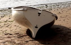 Boat sitting on the sand on the beach Stock Image