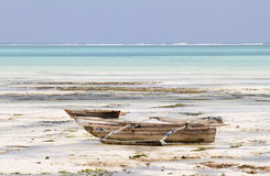 Boat sitting on a sea bottom while low tide Royalty Free Stock Images