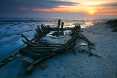 Boat skeleton on shore at sunset Stock Photography
