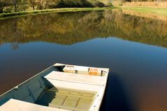 Boat at small pond. A row boat pull up onto the bank at a pond stock photos
