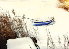 Boat in the snow at dawn on the river in winter Stock Photos