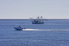 Boat Speeding Past Shrimp Boat royalty free stock photo