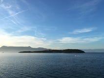 Boat speeding past Vidos Island, Greece Stock Images