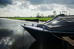 Boat standing on the water attached to the shore and covered wit Stock Photography