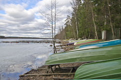 Boat station landscape in the border of Saaksjarvi Lake in Finla. Boats colored in different colors are stored along the icy border of the lake waiting for the royalty free stock photos