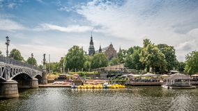 Boat station and street cafe in old part of Stockholm near Nordic Museum, view from the river, Sweden royalty free stock images