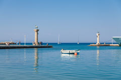 Boat and Statue Deer and hound and columns in Mandraki harbor. Royalty Free Stock Image