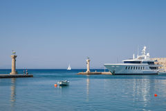 Boat and Statue Deer and hound and columns in Mandraki harbor. Royalty Free Stock Images