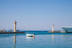 Boat and Statue Deer and hound and columns in Mandraki harbor. Stock Photography