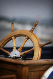 Boat steering wheel. Wooden steering wheel on an old sail boat Stock Image