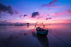 Boat in still waters, Vietnam at sunset Royalty Free Stock Images