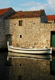 Boat before stone house. Boat be mirrored before stone house Royalty Free Stock Image