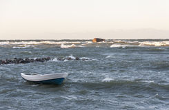 Boat in stormy sea. White fishing boat in stormy wavy sea Stock Photography