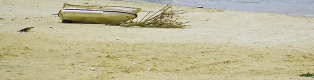 Boat stranded on the beach. Small wooden boat and litter on the beach Stock Image