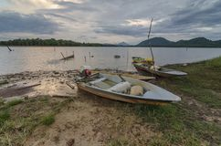 A boat stranded near the lake. During sunset near the lake with majestic clouds Royalty Free Stock Images