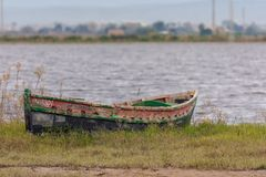Boat stranded on the shore of the lagoon in the natural park of Albufera, Valencia, Spain royalty free stock photography